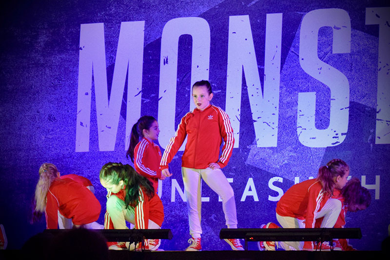 girls dancing on stage in matching red and white uniforms